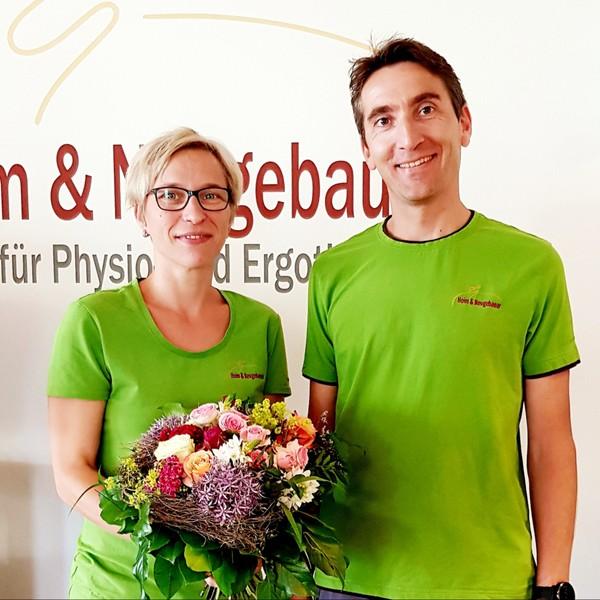 Praxisinhaber Frank Heim gratuliert Physiotherapeutin Andrea Schocker mit einem Blumenstraß zum 10 jährigen Praxisjubiläum